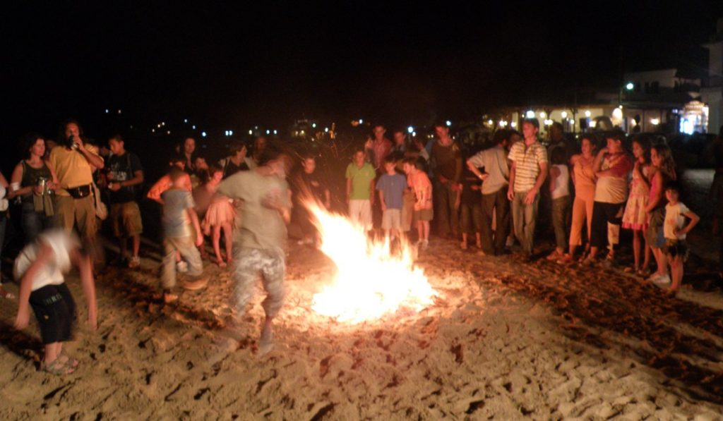 boys jumping bonfire